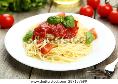 Spaghetti with tomatoes and basil on plate on grey wooden background - stock photo