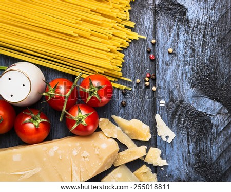Spaghetti with tomatoes and parmesan on blue wooden background, top view, copy space - stock photo