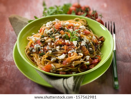 spaghetti with tomatoes cheese capers and arugula, selective focus - stock photo