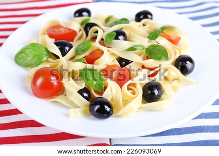 Spaghetti with tomatoes, olives and basil leaves on plate on napkin - stock photo