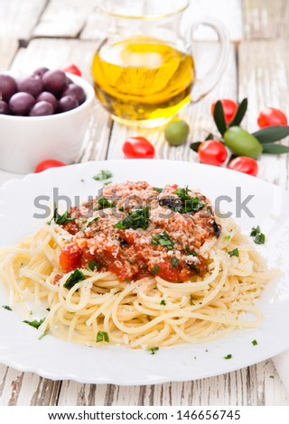 Spaghetti with tomatoes on wooden table - stock photo