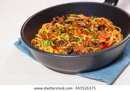 spaghetti with vegetables and minced meat in a frying pan