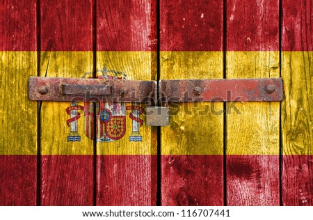Spain flag on the background of old locked doors