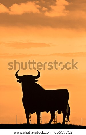 Spain, silhouette of a bull in the field in Andalucia. - stock photo