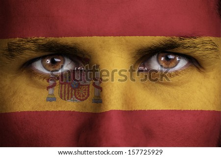 spain, spanish flag painted on the face of young man - stock photo