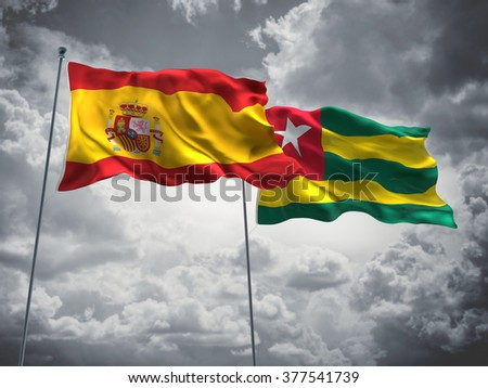 Spain & Togo Flags are waving in the sky with dark clouds