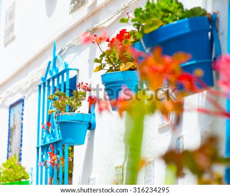 Spain, Torremolinos. Costa del Sol, Andalucia. Typical White Village with flower pots in facades at Spain. Beautiful street decorated with flowers in Spain. Tourism concept  - stock photo