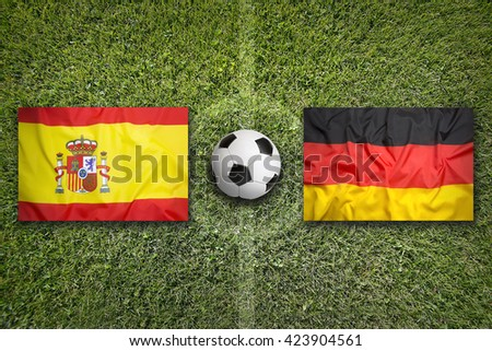 Spain vs. Germany flags on a green soccer field