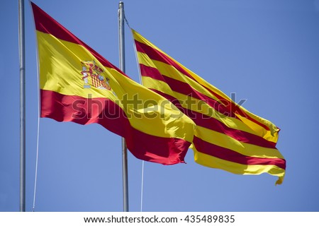 Spanish and Catalan flag flying together against blue sky on a bank building in Barcelona, Spain - stock photo