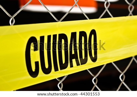 spanish caution tape over chain link fence - cuidado - stock photo