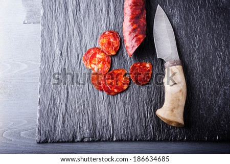 Spanish chorizo on a stone plate - stock photo