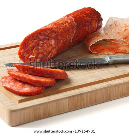 Spanish chorizo sausage with knife on wooden board, focus is on sausage - stock photo
