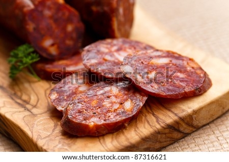 Spanish chorizo sausage with parsley on rustic board - stock photo