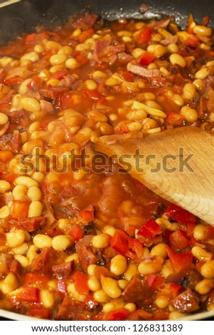 Spanish chorizo with baked beans, red peppers and onions - stock photo
