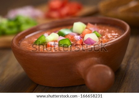 Spanish cold vegetable soup made of tomato, cucumber, bell pepper, onion, garlic and olive oil served in rustic bowl (Selective Focus, Focus on the front of the vegetables on the top of the soup) - stock photo