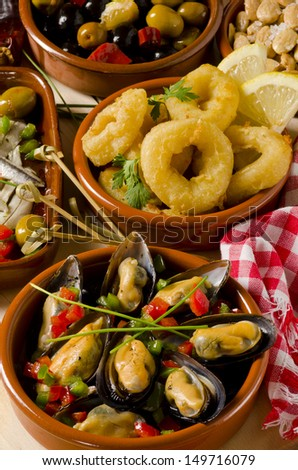 Spanish cuisine. Assortment of  Tapas including   Marinated Olives, Mussels in Sauce and  Fried Squid Rings. - stock photo