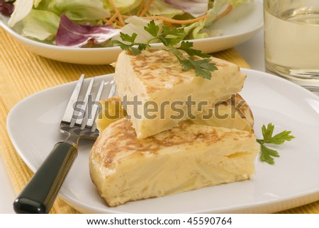 Spanish cuisine. Potatoes omelet served with salad.Tortilla espanola.