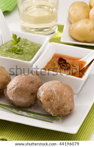 Spanish cuisine. Red mojo sauce and green mojo sauce with wrinkled potatoes served in a white bowl. Typical Canary hot sauce. Mojo picon and and mojo verde with papas arrugas. - stock photo