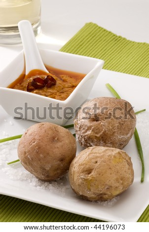 Spanish cuisine. Red mojo sauce and wrinkled potatoes served in a white bowl. Typical Canary hot sauce. Mojo picon and papas arrugas. - stock photo