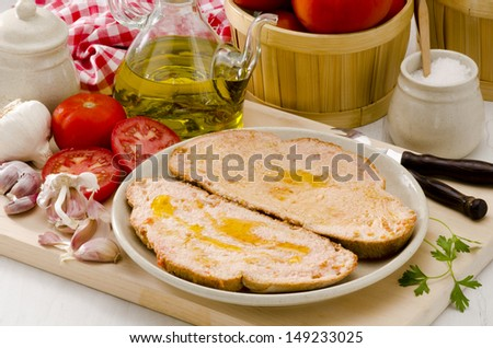 Spanish cuisine. Slices of tomato bread drizzled with olive oil. Selective Focus. Pa amb tomaquet. - stock photo