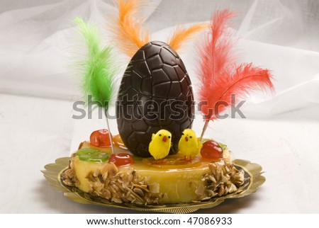 Spanish cuisine. Typical Easter cake  decorated with a chocolate egg and colorful feathers. Mona de Pascua.