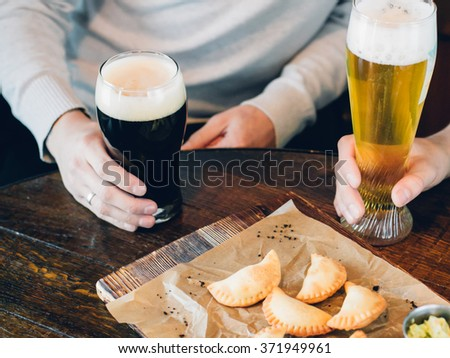 Spanish Empanadas with dark and light beer in a pub, male hands holding glasses - stock photo