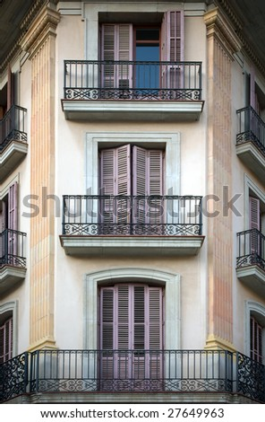 Spanish facade with balconies and doors painted in mauve color.