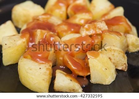 "Spanish food: delicious ""patatas bravas"", hot and spicy potatoes. - stock photo"