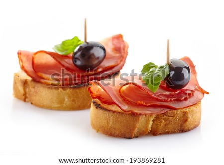 Spanish food tapas, Toast with serrano meat, olive and basil isolated on white - stock photo