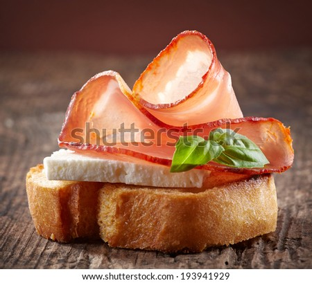 Spanish food tapas. Toasted bread with goat cheese and serrano ham - stock photo