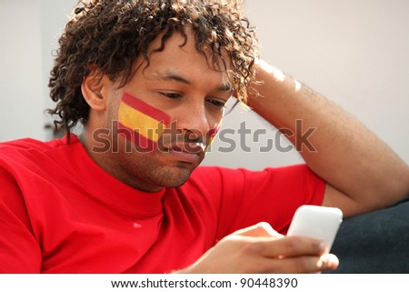 Spanish football supporter with mobile telephone