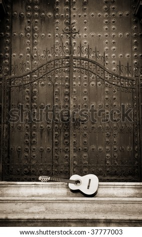 Spanish guitar in front of a cathedral doors - stock photo
