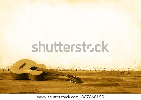Spanish guitar lying in front of a wall as background color sepia
