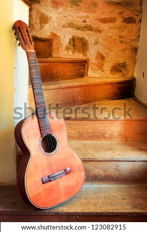 Spanish guitar on old spiral staircase vertical