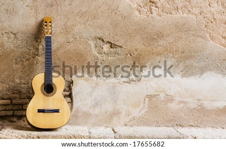 Spanish guitar on old wall, copy spaced. - stock photo