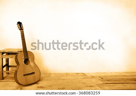 Spanish guitar propped in front of a white wall as background  sepia