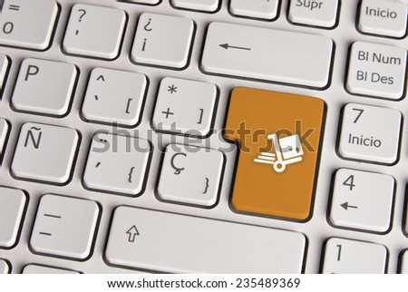 Spanish keyboard with delivery shipping cart icon over gold background button. Image with clipping path for easy change the key color and editing. - stock photo