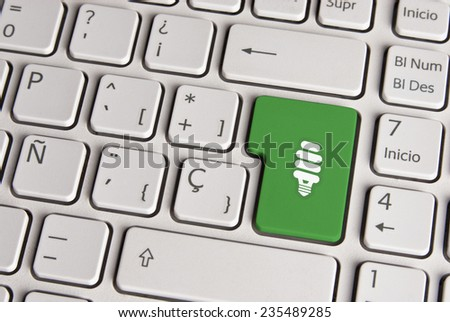 Spanish keyboard with eco energy light save bulb icon over green background button. Image with clipping path for easy change the key color and editing. - stock photo