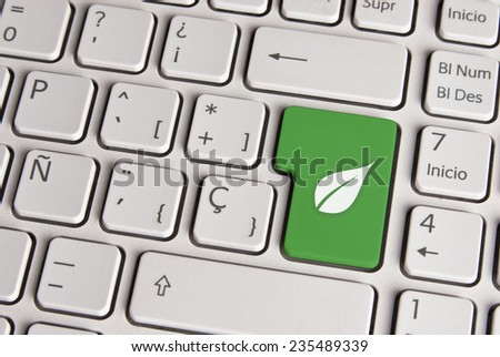 Spanish keyboard with eco friendly concept leaf icon over green background button. Image with clipping path for easy change the key color and editing. - stock photo