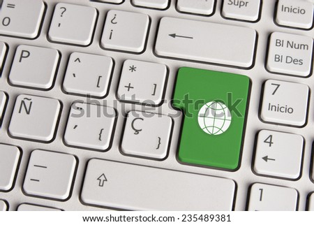 Spanish keyboard with global eco friendly world icon over green background button. Image with clipping path for easy change the key color and editing. - stock photo