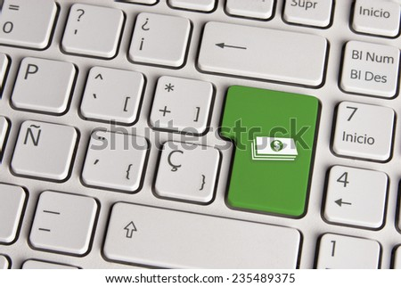 Spanish keyboard with money cash icon over green background button. Image with clipping path for easy change the key color and editing. - stock photo