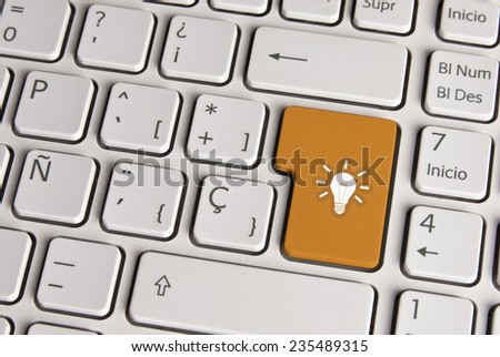 Spanish keyboard with new idea light bulb icon over gold background button. Image with clipping path for easy change the key color and editing.