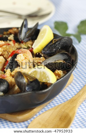 Spanish meal paella on a blue checkered tablecloth with wooden utensil.Shallow depth of field. - stock photo