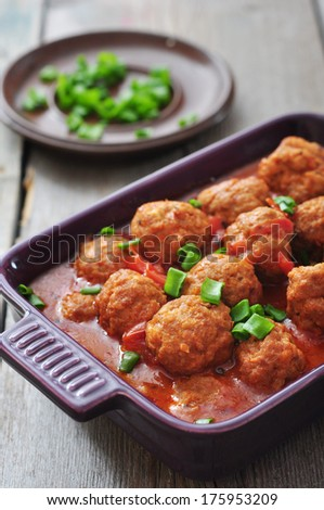 Spanish meatballs in ceramic baking mold on wooden background