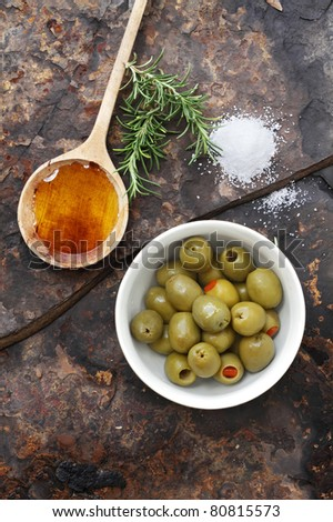Spanish olives with olive oil, rosemary, sea salt and olive on a rustic slate background. - stock photo