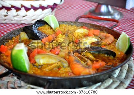 Spanish paella in pan on table - stock photo