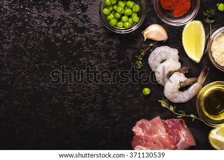 Spanish paella ingredients over black stone background. Top view - stock photo
