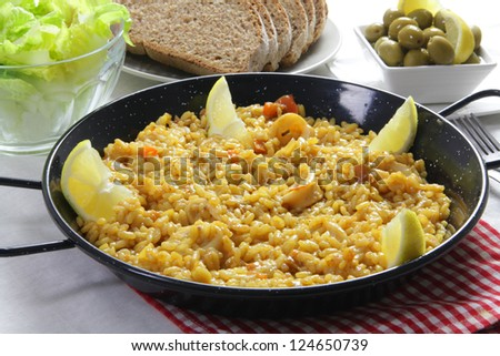spanish paella, olives, organic bread and salad - stock photo