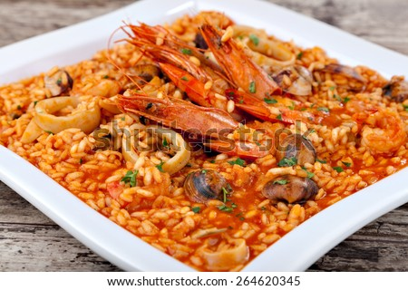 Spanish paella, rice with seafood on white plate. Close-up - stock photo