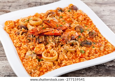 Spanish paella, rice with seafood on white plate. Close-up